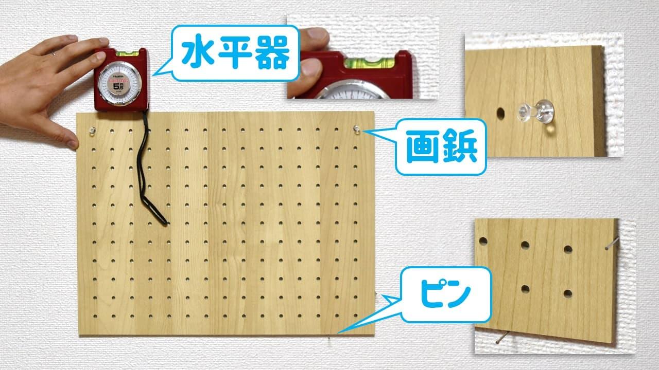 有孔ボードの位置決めに、ピン・画鋲・水平器を使っている様子