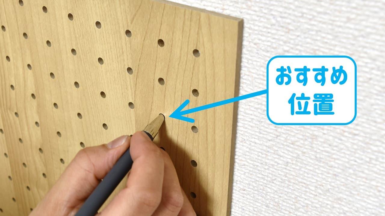 石膏ボード用パンチングボード止め具の取り付け場所に印付けする様子