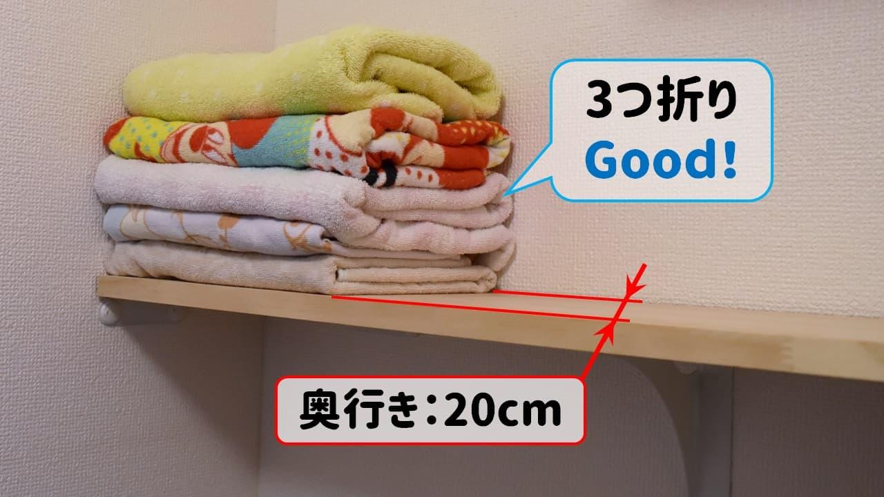 狭い賃貸の洗濯機上のDIY棚にバスタオルを置く様子