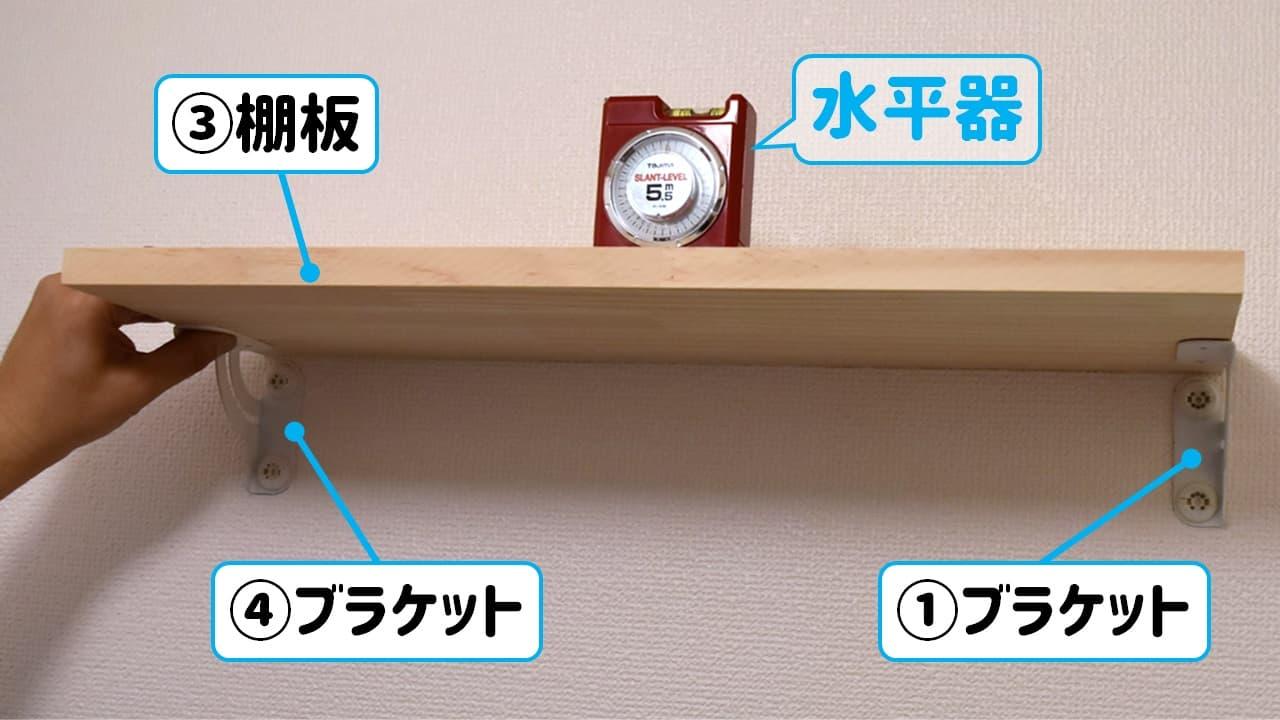 狭い賃貸の洗濯機上にDIY棚用ブラケットを棚板の水平を確認しながら仮固定する様子